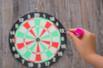 Hand pointing a dart to a target unfocused