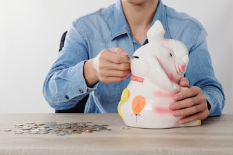 Hand putting money coins in to Elephant Bank money saving finance concept