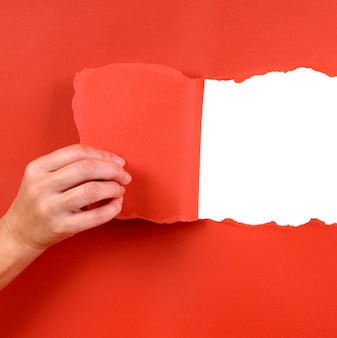 Hand tearing a paper