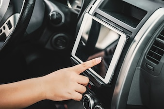 Hand touching a tablet in a car