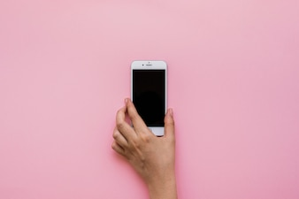 Hand with smartphone and pink background