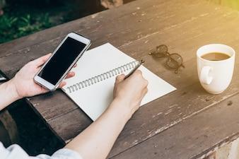ノートブックを書いて、ヴィンテージトーンで木製テーブルのバックホーミングで電話を持っている手の女性。