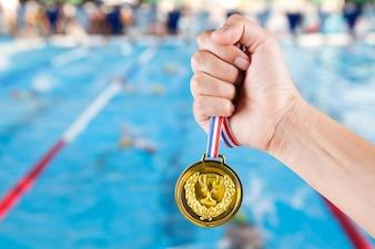горстка азиатского человека, держащего золотую медаль с размытым фоном плавательного бассейна и соревнований по плаванию.