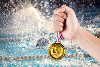 горстка азиатского человека, держащего золотую медаль с размытым фоном плавательного бассейна.