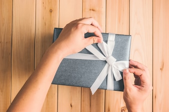 Hands adjusting the bow of a gift