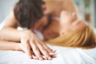 Hands close-up of a couple kissing in a bed