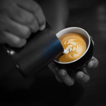 Hands filling a cup of coffee with milk