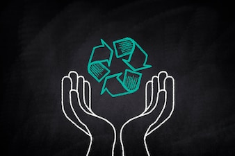 Hands holding a recycling symbol on a blackboard
