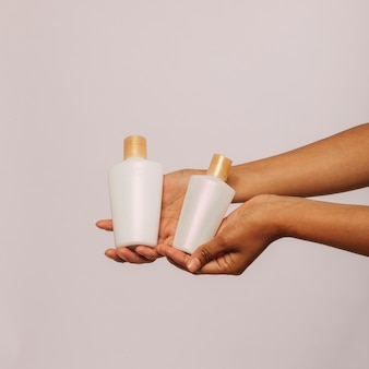 Hands holding cosmetic products