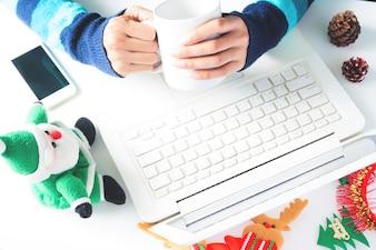 手のコーヒーを保持し、ラップトップを使用して、クリスマスの装飾とスマートフォン、ショッピングオンライン