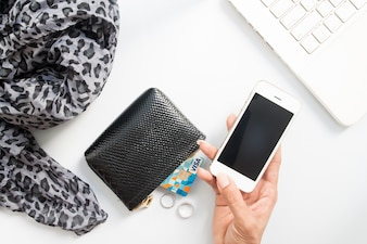 Hands holding mobile with credit cards in purse and using laptop. Online shopping