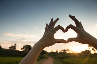 Hands in heart form love, silhouette hand make heart form with sun set