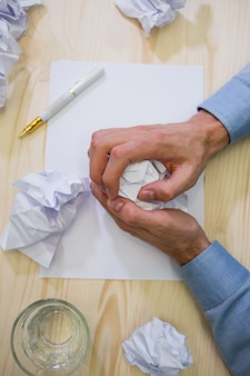 Hands of business executive making paper ball