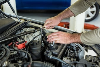 Hands of mechanic servicing a car