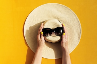 Hands of young girl holding straw hat and sunglasses on vibrant yellow background.