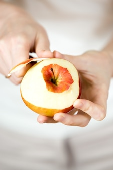 Hands peeling an apple