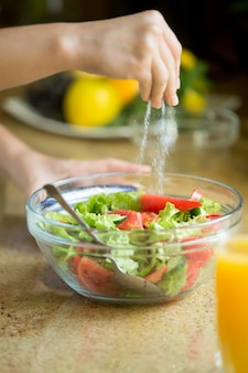 Hands salting a green salad