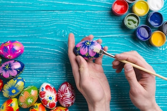 Hands with paint brush painting an easter egg