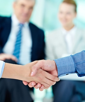 Handshake with businesspeople blurred background