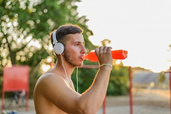 Handsome athlete drinking water after training.