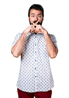 Handsome brunette man with beard making silence gesture