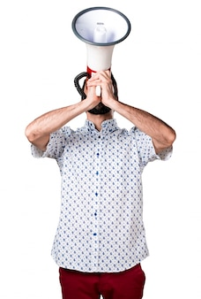 Handsome brunette man with beard shouting by megaphone