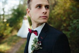 Handsome guy in tuxedo looking away standing