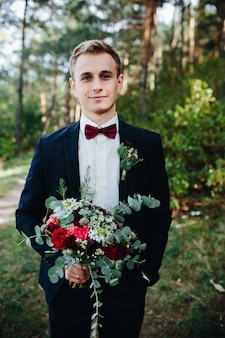 Handsome guy standing with bunch of flowers