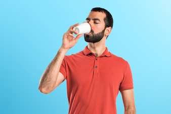Handsome man drinking coffee on colorful background