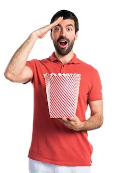 Handsome man eating popcorns