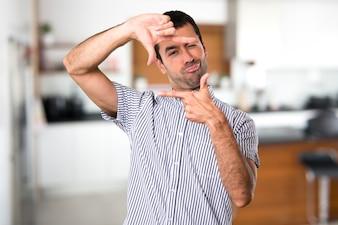 家の中で彼の指で集中しているハンサムな男