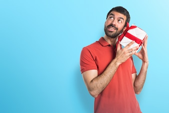 Handsome man holding a gift on colorful background