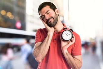 Handsome man holding vintage clock on unfocused background