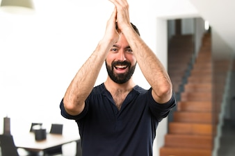 Handsome man with beard applauding inside house