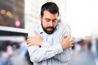 Handsome man with beard freezing on unfocused background