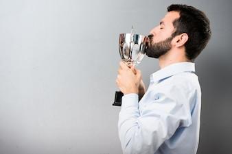 Красивый человек с бородой, проведение трофей на текстурированном фоне