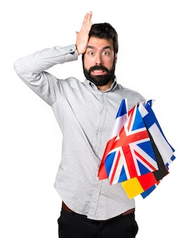 Handsome man with beard holding many flags and having doubts