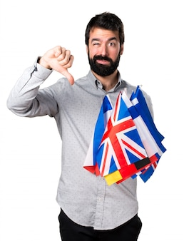 Handsome man with beard holding many flags and making bad signal
