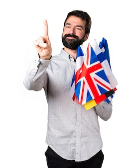 Handsome man with beard holding many flags and touching on transparent screen