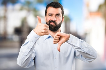Handsome man with beard making good-bad sign on unfocused background