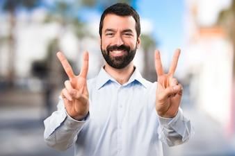 Красивый мужчина с бородой, делая жест победы на нефокусированном фоне
