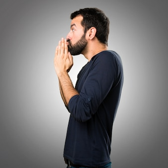 Handsome man with beard pleading on grey background