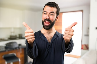 Handsome man with beard with thumb up inside house