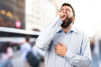 Красивый мужчина с бородой, зевая на нефокусированном фоне