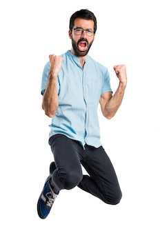 青い眼鏡を持って飛び跳ねるハンサムな男