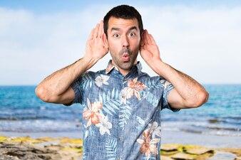 Красивый мужчина с цветной рубашкой, слушать что-то на пляже