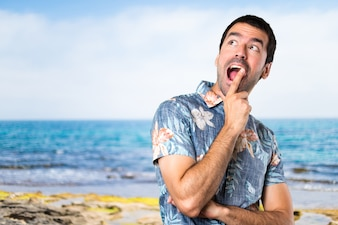 Handsome man with flower shirt making surprise gesture at the beach