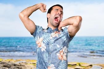 Красивый мужчина с цветочной рубашкой, зевая на пляже
