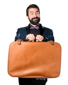 Handsome man with sequin jacket holding a vintage  briefcase
