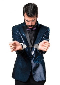Handsome man with sequin jacket with handcuffs